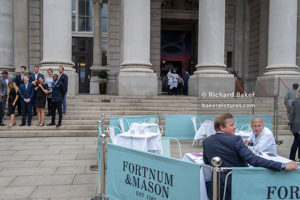 Diners and drinkers sit within street barriers where Fortnum & Masons have set up an outdoor restaurant and bar in front of the Royal Exchange at Bank, in the City of London, during the Coronavirus pandemic, on 9th September 2020, in London, England.