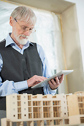 Architect with digital tablet at construction site of new building