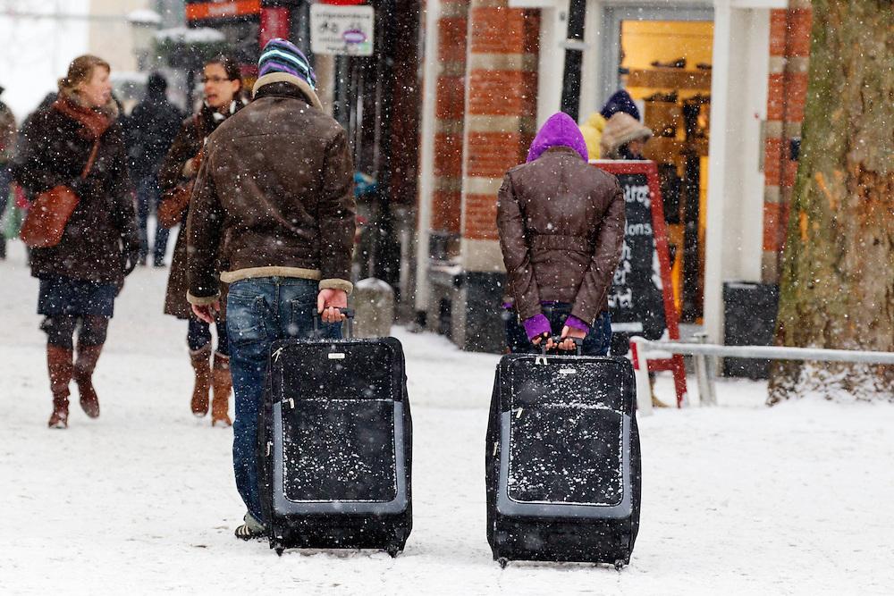 Twee reizigers ploeteren bij de Servetstraat in Utrecht met hun koffers door de sneeuw.<br /> <br /> Two travellers are walking with their suitcases in the snow at the Servetstraat Utrecht.