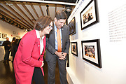 US Chess Executive Director Carol Meyer (left) and US Chess Senior Director of Strategic Communication Dan Lucas look at a photograph at the World Chess Hall of Fame in St. Louis where a new chess history exhibition, US Chess: 80 Years—Promoting the Royal Game in America, opened there with a free opening reception event on March 6, 2019. The photo shows an eight year old girl defeating a former NFL football player (who is also a mathematics whiz) in a game of chess. The chess exhibit will be on display through October 27, 2019. <br /> (Tim Vizer/AP Images for  World Chess Hall of Fame)