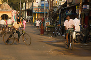 Cyclists on the main street of the sleepy temple town of Swamimalai, Tamil Nadu, India..Swamimalai is a renown centre for bronze casters that still use traditional methods of 'lost wax' casting that date back to the great Chola kings a thousand years ago.Cyclists on the main street of the sleepy temple town of Swamimalai. .