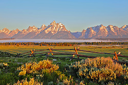 """Grand Tetons at daybreak, a buckrail fence is a reminder of Grand Teton National Park's ranching legacy.<br /> <br /> For production prints or stock photos click the Purchase Print/License Photo Button in upper Right; for Fine Art """"Custom Prints"""" contact Daryl - 208-709-3250 or dh@greater-yellowstone.com"""