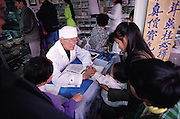 A traditional medicine doctor surrounded by his patients in the Fu Lin Tang Pharmacy. The doctor, and all those in the line, listen to a series of health ailments, after which the doctor then prescribes a specific prescriptions of herbs and insects, among other natural ingredients. Kunming, China. (Man Eating Bugs page 105 Top)