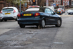 A car splashes across a pothole on Sidmouth Road in Willesden Green West London as the recent cold, wet weather has given rise to the increase in potholes and road surface deterioration in the capital. London, March 28 2018.