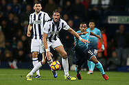 Jonas Olsson of West Bromwich shields the ball from Wayne Routledge of Swansea city. Premier league match, West Bromwich Albion v Swansea city at the Hawthorns stadium in West Bromwich, Midlands on Wednesday 14th December 2016. pic by Andrew Orchard, Andrew Orchard sports photography.