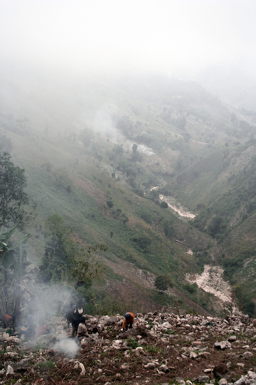 An eery chanting pierces the still air as locals work in groups, clearing trees and burning vegetation. The chanting keeps morale high throughout a long working day. Haiti