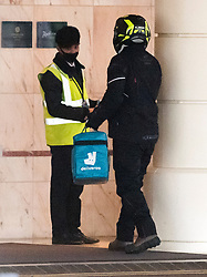 © Licensed to London News Pictures. 25/02/2021. London, UK.  A Deliveroo driver delivers food at breakfast time to the Radisson hotel near Heathrow Airport. New quarantine measures were introduced for travellers form red list countries, who are required to isolate for ten days in a hotel at a cost of £1,750 per person. Photo credit: Ben Cawthra/LNP