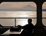A silhouetted commuter relaxes during a ferry crossing of Puget Sound, Washington, USA.  Mount Rainier and another ferry can be seen in the background.