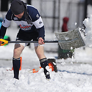 A Mystic River player clears the sideline of snow during the Men's Club Division game with Connecticut Yankees at the Four Leaf 15s Rugby Tournament which attracted over 60 clubs teams from New York and Interstate. Randall's Island Park, New York,  USA. 21st March 2015. Photo Tim Clayton