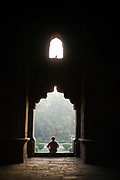 A man sits on the steps of the Bara Gumbad, Lodhi Gardens, New Delhi, India