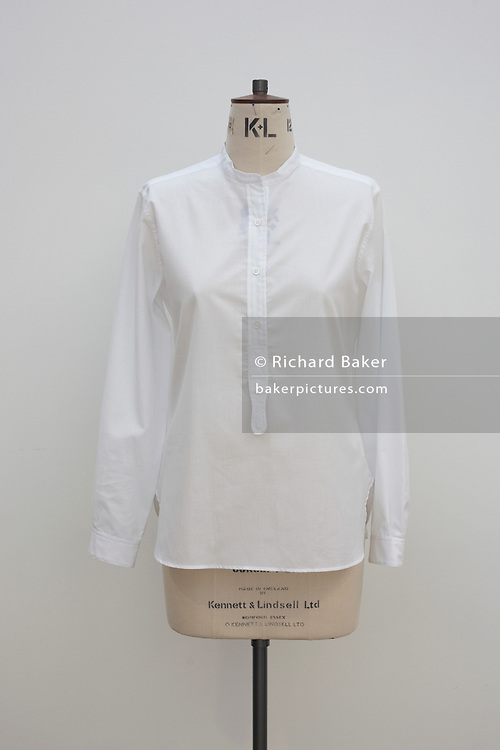 "A beautifully simple white cotton shirt by couturier Margaret Howell is displayed in the company's workshop factory in Edmonton, North London. England. Ironed without creases, the garment has been set on a dress making tailor's dummy made by Kennett and Lindsell of Romford Essex. The pure white shirt is seen against a similarly-toned white wall and lit by daylight. Howell is one of Britain's more understated of couture brands alongside more flamboyant personalities. Howell admits to being ""inspired by the methods by which something is made .. enjoying the tactile quality of natural fabrics such as tweeds, linen and cotton in a relaxed, natural and lived in look."""