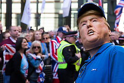 London, UK. 14 May, 2019. A man wearing a Donald Trump mask waits with other supporters of Tommy Robinson outside the Old Bailey for the former English Defence League leader to appear following a hearing during which two High Court judges declared that fresh proceedings may be brought against him for an alleged contempt of court over the filming of people involved in a criminal trial.