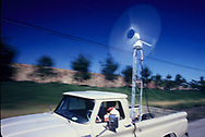 An inventor uses his truck to calculate the strength of the wind for a test of a wind energy producing device in October 1979<br /> Photo by Dennis Brack