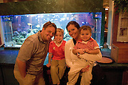 Happy family in front Aquarium after a wonderful meal at Brewmaster Steak House.  Indian Rocks Beach Tampa Bay Area Florida USA