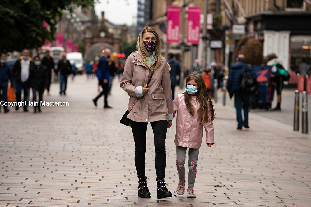 Glasgow, Scotland, UK. 17 July, 2020.  Images from Glasgow city centre as covid-19 restrictions are relaxed and  the public are out and about shopping and at work. Pictured; Mother and daughter walking on Buchanan Street wearing face coverings. Iain Masterton/Alamy Live News