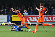 AFC Wimbledon striker Kweshi Appiah (9) going down after challange from Southend United defender Harry Kyprianou (27) during the EFL Sky Bet League 1 match between AFC Wimbledon and Southend United at the Cherry Red Records Stadium, Kingston, England on 24 November 2018.