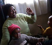 Mama Ester is playing with two of the children at her creche in Khayelitsha township in Cape Town, where over a million people live in the extreme poverty..