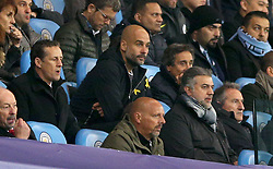 Manchester City manager Pep Guardiola sits in the stands after being sent off for his complaints to officials at the end of the first half