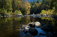 Fall colors begin to emerge on a stretch of the Linville River near the Pinch In Trail in the Linville Gorge, North Carolina