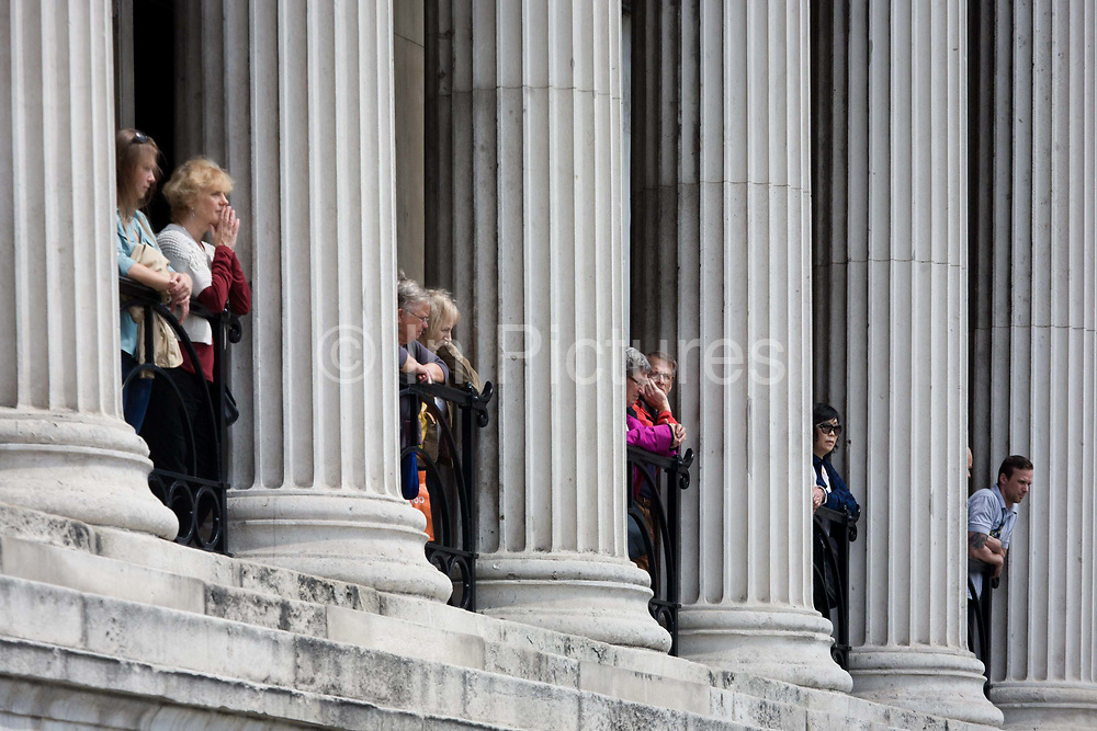 Visitors to the National Gallery admire the view from beneath classical pillars in Trafalgar Square. Fluted columns in the classical style are seen in this central London landmark known for its galleries and fine buildings, laid out in the Victorian period. Tourists lean against the railings to view street entertainment on the pavement below.
