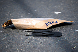 © Licensed to London News Pictures. 07/07/2016. London, UK. A baseball cap lying next to an evidence bag at the scene where a man was struck by a car following an assault on Harrow Road in Harlesden, north west London. Photo credit: Ben Cawthra/LNP