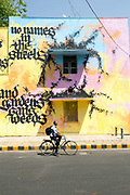 A cyclist passes a painting and poem by Niels Shoe Meulman on display in the Lodhi Colony area of New Delhi  designated Indias first ever public art district.