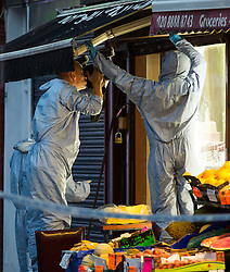 © Licensed to London News Pictures. 10/07/2015. London, UK. Forensics officers photograph  the exterior of a grocery store at the scene. Police and forensics forensics at the scene of a double shooting on Lordship Lame in Wood Green, north London in which a man has died and a woman is currently being treated in hospital.  Photo credit: Ben Cawthra/LNP
