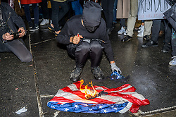 November 9, 2016 - New York, New York, United States - A demonstrator burns a flag in front of Trump Tower. An estimate of ten thousand demonstrators took the streets of Manhattan on Wednesday night and converged outside Trump Tower in Midtown to protest the election of Donald J. Trump as president. (Credit Image: © Erik Mcgregor/Pacific Press via ZUMA Wire)