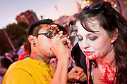 """Oct. 30, 2009 -- PHOENIX, AZ: MICHAEL GARCIA helps THANIA BETANCOURT put on her makeup before the Zombie Walk in Phoenix Friday. About 200 people participated in the first """"Zombie Walk"""" in Phoenix, AZ, Friday night. The Zombies walked through downtown Phoenix """"attacking"""" willing victims and mixing with folks going to the theatre and downtown sports venues.  Photo by Jack Kurtz"""