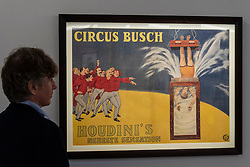 """© Licensed to London News Pictures. 24/09/2021. LONDON, UK. A staff member views a German vintage poster of """"Harry Houdini Upside Down in The Water Torture Cell"""". Preview of a collection spanning the history of magic from celebrity magician Ricky Jay.  The works are being shown in Sotheby's, New Bond Street, ahead of their auction in New York on 27 and 28 October.  Photo credit: Stephen Chung/LNP"""