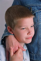 Portrait of young boy with adult's arm around him,