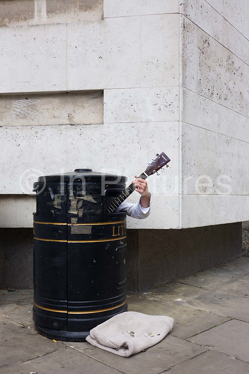 A street busker hides in a litter bin to earn extra cash as passers-by hear his music on a Cambridge pavement. Playing his acoustic instrument we see only the man's left hand grasping the neck and frets and strings of the guitar. At the foot of the bin there is a blanket with only a few coins to show for all the effort. Quite how he managed to climb into the receptacle is unclear although it is possible the bin has been doctored, pulling apart so his body could enter.