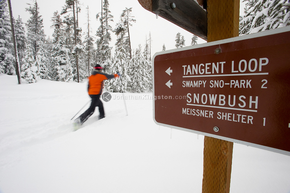 One young woman cross country skis in the snow past a trail sign in Bend, Oregon. (releasecode: jk_mr1033) (Model Released)