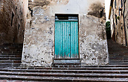A bright blue door framed by steps on a shadowy small street, in the Italian village of Corinaldo, in the Marche region