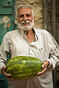 A trader on a stall at the Mahane Yahuda Market holds a melon, Jerusalem, Israel