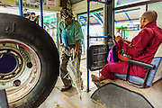 19 JUNE 2013 - YANGON, MYANMAR:  A man walks between a Buddhist monk and a spare tire while he boards a bus in Yangon. Yangon buses are generally overcrowded and in poor repair but as the economy improves newer, but still used, Japanese and Korean buses are being imported. Hundreds of bus routes criss-cross Yangon, providing the cheapest way of getting around the city. Most fares are less than the equivalent of .20¢ US.  PHOTO BY JACK KURTZ