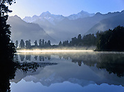 Mount Tasman and Aoraki/Mount Cook (left to right) reflect in Lake Matheson, near Fox Glacier, Westland Tai Poutini National Park, West Coast of South Island, NEW ZEALAND. In 1990, UNESCO honored Te Wahipounamu - South West New Zealand as a World Heritage Area. Published in Sierra Magazine, Sierra Club Outings January/February 2002.