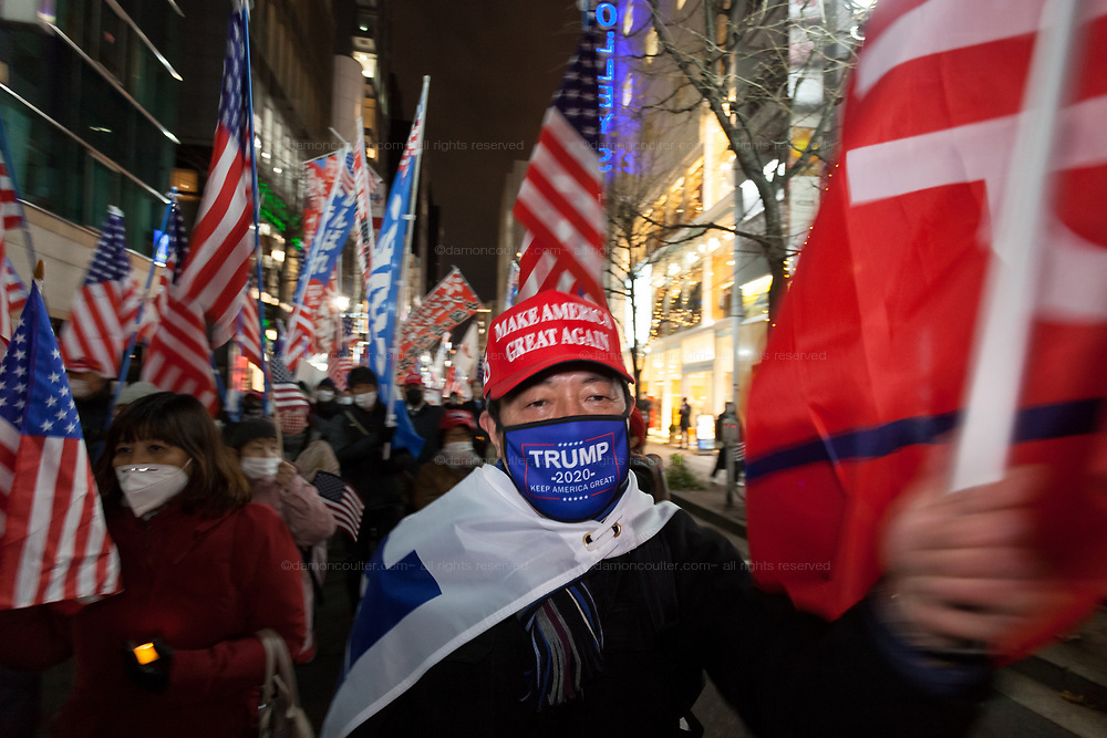 """A Japanese man, wearing  a Make America Great Again baseball cap is one of several hundred people, taking part in a """"March For Trump"""" rally  in support of the out-going United States President, Donald Trump. Tokyo, Japan. Wednesday January 6th 2021. The rally of mostly Japanese people took place as part of a similar rally by Trump-supporters in Washington DC as the results of the 2020 US Presidential election were confirmed."""