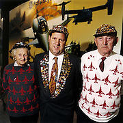 A family of three members covered with aviation and aerospace badges and knitted-plane jumpers during the bi-annual aerospace industry expo at the Farnborough airshow in southern England. Eccentric and obsessive, the family members look odd and ill-at-ease with their matching jumbers and adorned with dozens of collectable badges and pins loved by aviation groupies.