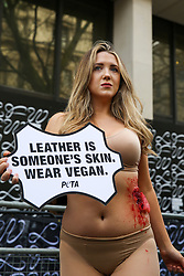 © Licensed to London News Pictures. 14/02/2020. London, UK. A half naked PETA (People for the Ethical Treatment of Animals) activist holds a sign 'Leather Is Someone's Skin. Wear Vegan' during a protest at start of London Fashion Week against the use of animal products in the leather industry. Photo credit: Dinendra Haria/LNP