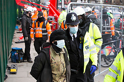 © Licensed to London News Pictures.31/01/2021, London,UK. A protestor is detained from Euston Square Gardens in central London after protesting on a tree since Wednesday. Eco-activists are living in increasingly unstable tunnels beneath the square. Photo credit: Marcin Nowak/LNP