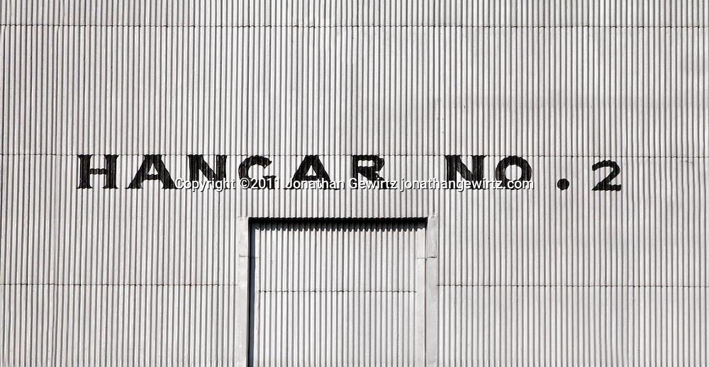 Front entrance with closed door of a large, corrugated metal aircraft hangar. WATERMARKS WILL NOT APPEAR ON PRINTS OR LICENSED IMAGES.