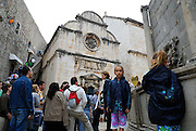 Tourists inside Dubrovnik old town, with city wall and Church of Saint Saviour in background
