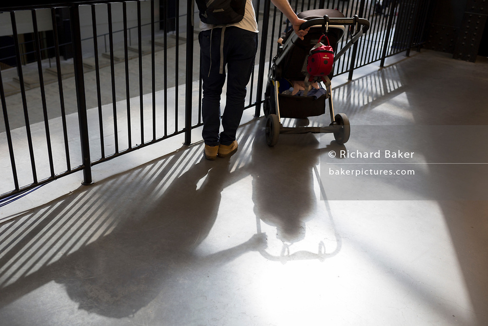 A father holds his child's buggy near railings that overlook the Turbine Hall of Tate Modern on the Southbank, on 14th May 2017, in London, England.