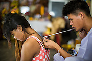 "22 MARCH 2013 - NAKHON CHAI SI, NAKHON PATHOM, THAILAND: A woman gets a sacred Sak Yant tattoo at Wat Bang Phra. Wat Bang Phra is the best known ""Sak Yant"" tattoo temple in Thailand. It's located in Nakhon Pathom province, about 40 miles from Bangkok. The tattoos are given with hollow stainless steel needles and are thought to possess magical powers of protection. The tattoos, which are given by Buddhist monks, are popular with soldiers, policeman and gangsters, people who generally live in harm's way. The tattoo must be activated to remain powerful and the annual Wai Khru Ceremony (tattoo festival) at the temple draws thousands of devotees who come to the temple to activate or renew the tattoos. People go into trance like states and then assume the personality of their tattoo, so people with tiger tattoos assume the personality of a tiger, people with monkey tattoos take on the personality of a monkey and so on. In recent years the tattoo festival has become popular with tourists who make the trip to Nakorn Pathom province to see a side of ""exotic"" Thailand. The 2013 tattoo festival was on March 23.    PHOTO BY JACK KURTZ"