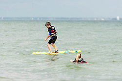 © Licensed to London News Pictures. 14/06/2014. Ryde, Isle of Wight, UK. A brother and sister surfing in the sea on a hot sunny morning.  The UK is experiencing a period of hot sunny weather with temperatures over the weekend expected to reach 74 F (23 C).  Photo credit : Richard Isaac/LNP