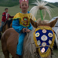 A young, costumed  rider poses after winning a 20km race at a traditional naadam festival on a remote pass near Muren, Mongolia. The horse's medals are from earlier races and are a great source of family honor. The medals are from his previous victories, during which he rode barefoot and bareback to save weight.