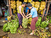 "10 JUNE 2014 - YANGON, MYANMAR:   Merchants buy and sell bananas on the banana jetty. The ""banana jetty"" is on the Yangon River north of central Yangon on Strand Road. Bananas, coconuts and other fruit are brought in here from upcountry, sold and reshipped to other parts of Myanmar (Burma). All of the labor here is done by hand. Porters carry the produce to the jetty and porters load the boats before they steam upriver.   PHOTO BY JACK KURTZ"