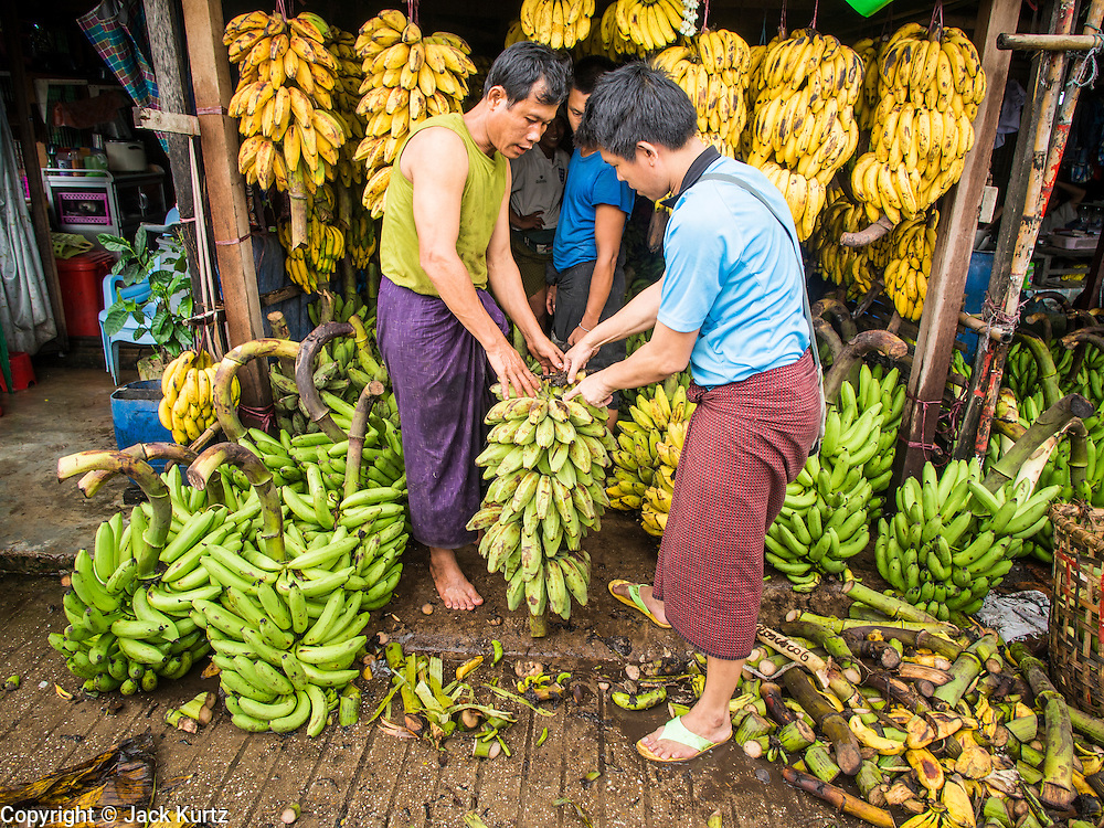 """10 JUNE 2014 - YANGON, MYANMAR:   Merchants buy and sell bananas on the banana jetty. The """"banana jetty"""" is on the Yangon River north of central Yangon on Strand Road. Bananas, coconuts and other fruit are brought in here from upcountry, sold and reshipped to other parts of Myanmar (Burma). All of the labor here is done by hand. Porters carry the produce to the jetty and porters load the boats before they steam upriver.   PHOTO BY JACK KURTZ"""