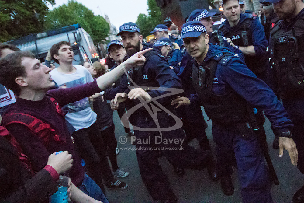 London, May 27th 2015. Police surround demonstrators outside Downing Street as they protest against the Tories' ongoing campaign of austerity on the day the Queen delivered her speech to Parliament